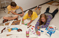 Sophomores Garrett Guilmett, Brady Caldwell and Emina Karabegovic paint Toy Story characters for their Homecoming float Thursday evening at Laconia High School.  (Karen Bobotas/for the Laconia Daily Sun)