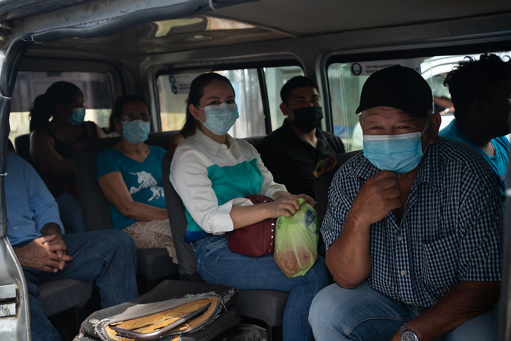 Passengers wearing masks inside a 'micro' in Chamelcón, San Pedro Sula.