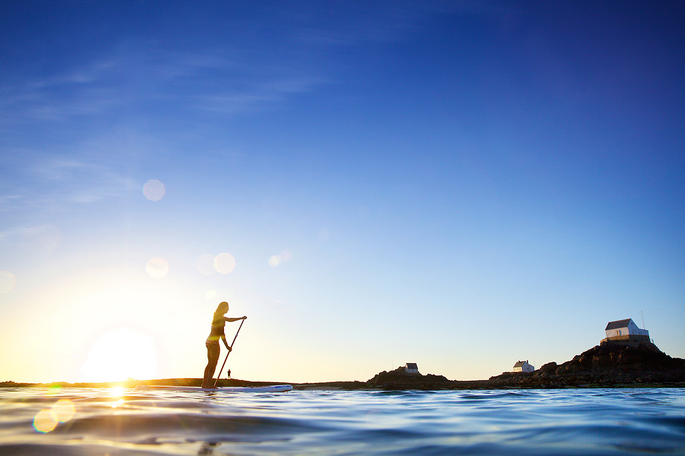 Silhouette of a girl paddle boarding at sunset, at the tourist destination the Ecrehous, off the coast of Jersey, CI
