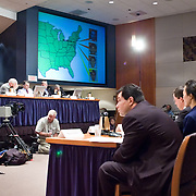 """Commission staffers present Staff Statement No. 16, """"Outline of the 9/11 Plot."""" On the screen is a map showing the flight paths of the hijacked planes. The 9/11 Commission's 12th public hearing on """"The 9/11 Plot"""" and """"National Crisis Management"""" was held June 16-17, 2004, in Washington, DC."""