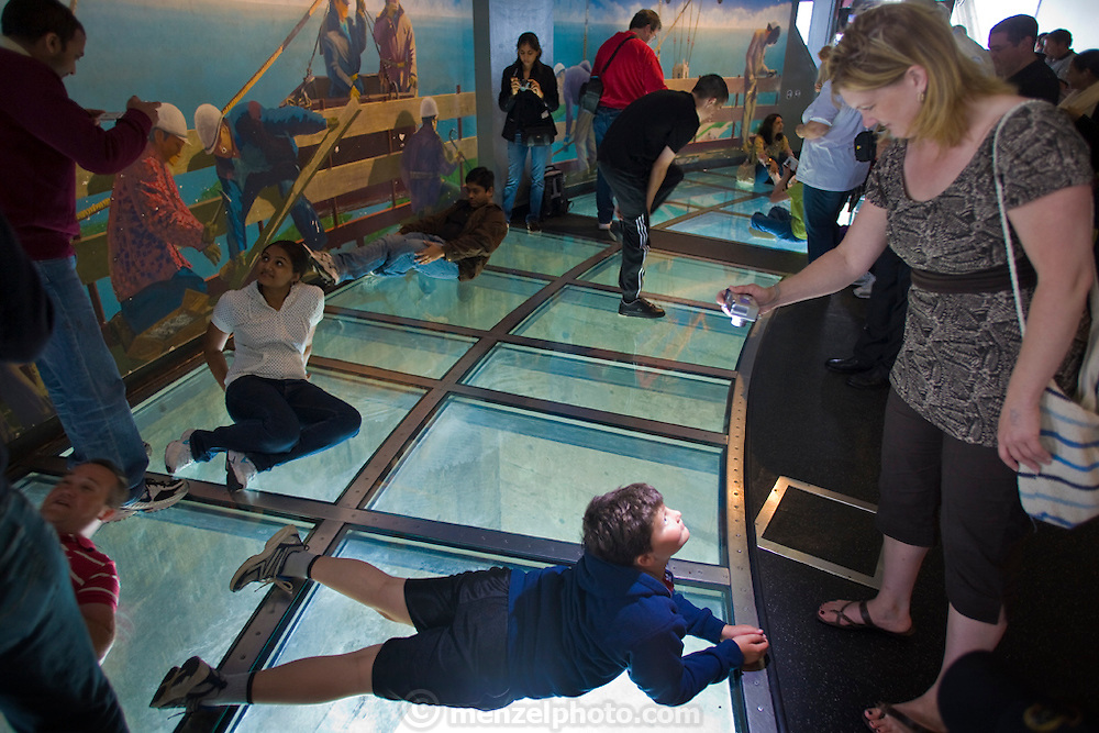 Visitors view the city of Toronto from the viewing tower at CN Tower in Toronto, Canada, where Neil Jones works as a director of operations. Visitors take photos on the glass floor. (Neil Jones is featured in the book What I Eat: Around the World in 80 Diets.)