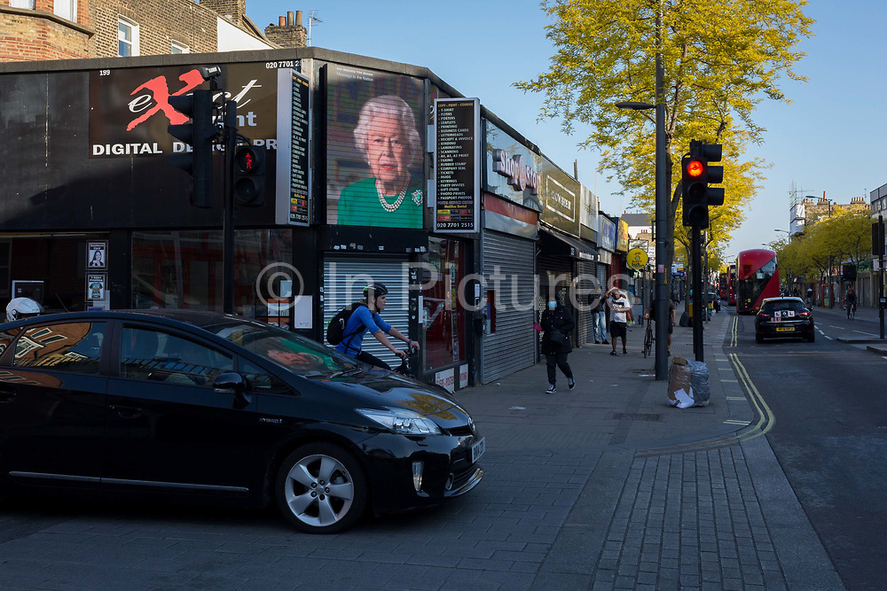 As the number of new Coronavirus cases in the UK climbs to 201,101, with UK deaths now standing at 30,076 - the highest recorded in Europe, <br /> an image of Queen Elizabeth during her recent address to the nation, looks out on to the Walworth Road in south London, during the continuing Covid lockdown, on 6th May 2020, in south London, England.