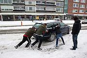 Jongens duwen een auto die vastzit op de Amsterdamsestraatweg in Utrecht. De hevige sneeuwval levert de nodige problemen op in Nederland.<br /> <br /> Boys are pushing a car back on the road at the Amsterdamsestraatweg in Utrecht. Due to the heavy snowfall this winter traffic is having a lot of problems.
