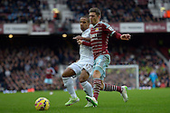 Aaron Cresswell of West Ham United competes with Wayne Routledge of Swansea City. Barclays Premier league match, West Ham Utd v Swansea city at the Boleyn ground, Upton Park in London on Sunday 7th December 2014.<br /> pic by John Patrick Fletcher, Andrew Orchard sports photography.
