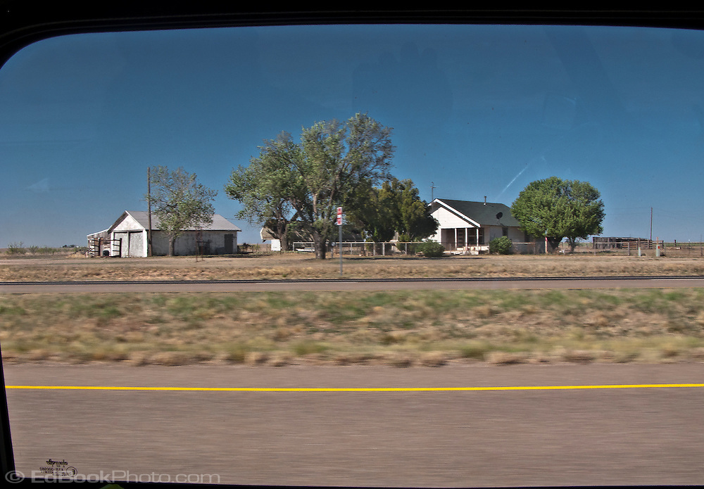 a lone farmhouse in flat rural west Texas along interstate 20 panorama framed in a Mini Cooper automobile window
