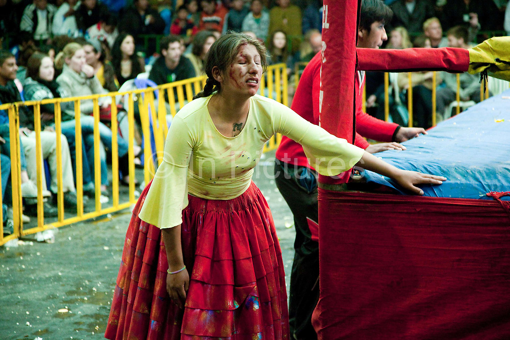 Alicia Flores female wrestler looking injured and angry out of ring fake blood, crowd in background. Lucha Libre wrestling origniated in Mexico, but is popular in other latin Amercian countries, including in La Paz / El Alto, Bolivia. Male and female fighters participate in the theatrical staged fights to an adoring crowd of locals and foreigners alike.