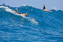Surfer couples, enjoying riding rare big ocean waves in Kona Coast, Keauhou Bay, Big Island, Hawaii, Pacific Ocean.