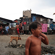 A young boy cries in the Baseco area of Tondo, one of the worst slum areas of Manila as youths play basketball in the background on October 9, 2008 in Manila, the Philippines. Photo Tim Clayton