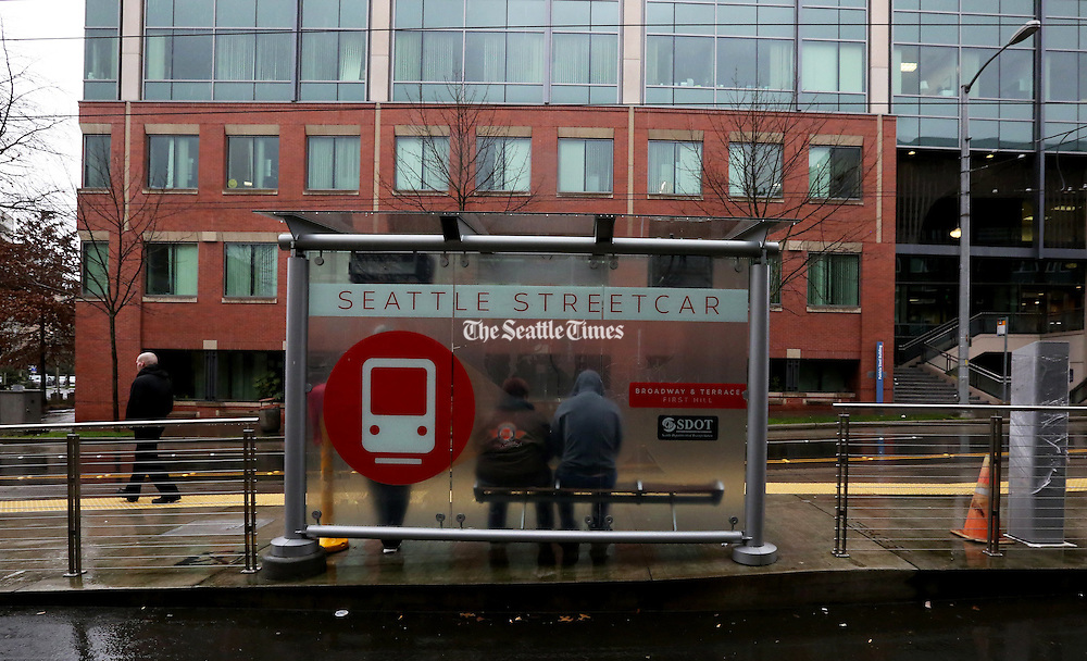 Passengers wait at the stop for the streetcar. (Alan Berner/The Seattle Times)