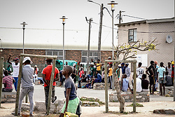 """Police Operations and Essential Services Personnel operating under lockdown period in Fish Hoek and Masipumelela in the Cape Peninsula, near Cape Town, Western Cape, South Africa, RSA<br /> <br /> Mister Khosa, a handiman from Zimbabwe, explains: """"there is a whole lot of michieviousness here with people not keeping their 1m distance"""", pointing across at a small square where a soccer match ebbs and flows."""