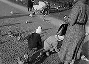 Children Feeding Pigeons as Guardian Watches, Berlin, c. 1931