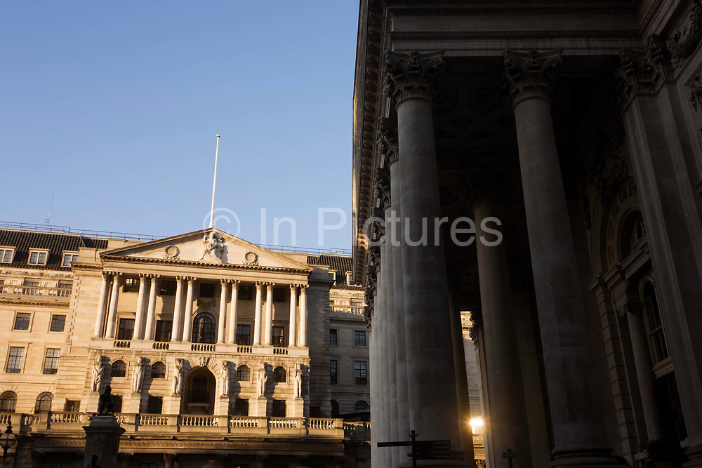 Looking across Bank Triangle, we look up towards the Bank of England and the pillars of Cornhill. It is later afternoon and winter light is striking the architecture of this famous London landmark. Ahead are the converging columns of the famous Bank of England and to the right Cornhill Exchange at Bank Triangle in the City Of London, the financial district, otherwise known as the Square Mile. This perspective of suggests a bank and its architecture looking powerful and influential in the UK's economy. The pillars give a sense of establishment, a scene of classic stability and strength.