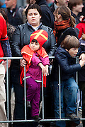 Boy wearing St. Nicolas mitre and cape at Sinterklaas parade, Amsterdam at Sinterklaas parade, Dam Square, Amsterdam, 14th November 2010. Sinterklaas, the basis for Santa Claus in other countries, arrives from Spain by boat,  accompanied by Black Peter, played by multitudes of white Dutch people in blackface - a tradition that evokes some controversy. Contrary to traditions of Santa Claus elsewhere, Sinterklass arrives by boat, then rides through the streets on his grey horse, Amerigo,  in mid-November, bringing in the Christmas season. The Zwarte Pieten (Black Peters) distribute sweets and gingerbread cookies to the crowd along the parade route.