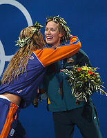 Gold Medal winner Jodie Henry (Australia) recieves congratulations from Inge de Bruijn (Holland) on the medal podium of the Womens 100m Freestyle Final. Swimming , Athens Olympics, 19/08/2004. Credit: Colorsport / Matthew Impey DIGITAL FILE ONLY