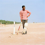 Portrait of a young man with cricket bat, Odayam beach, Kerala, India