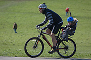 As the UK government considers further restrictions of movement in public places during the Coronavirus pandemic, south Londoners mindful of the need for social distancing, a father cycles with a child on the back of his bike in Brockwell Park in Herne Hill, on 23rd March 2020, in London, England.