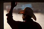 Man with cowboy hat and cigarette smoke riding ferry boat across Yangon River