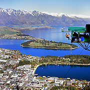 A participant jumps from the famous AJ Hackett Bungy Jump ' The Ledge' above Queenstown, New Zealand. The Bungy jump comes equipped with a runway to launch out 400 metres over Queenstown. with the snow capped Remarkables Mountain Range providing a stunning backdrop. Queenstown, Central Otago, South Island, New Zealand. Photo Tim Clayton