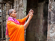 "14 MARCH 2105 - SIEM REAP, SIEM REAP, CAMBODIA: A Buddhist monk takes pictures with his smart phone in Bayon, one of the temples in Angkor Thom, a part of the Angkor Wat complex. Bayon was built in 12th or 13th century CE. The area known as ""Angkor Wat"" is a sprawling collection of archeological ruins and temples. The area was developed by ancient Khmer (Cambodian) Kings starting as early as 1150 CE and renovated and expanded around 1180CE by Jayavarman VII. Angkor Wat is now considered the seventh wonder of the world and is Cambodia's most important tourist attraction.   PHOTO BY JACK KURTZ"