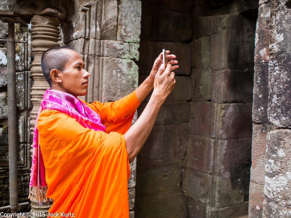"""14 MARCH 2105 - SIEM REAP, SIEM REAP, CAMBODIA: A Buddhist monk takes pictures with his smart phone in Bayon, one of the temples in Angkor Thom, a part of the Angkor Wat complex. Bayon was built in 12th or 13th century CE. The area known as """"Angkor Wat"""" is a sprawling collection of archeological ruins and temples. The area was developed by ancient Khmer (Cambodian) Kings starting as early as 1150 CE and renovated and expanded around 1180CE by Jayavarman VII. Angkor Wat is now considered the seventh wonder of the world and is Cambodia's most important tourist attraction.   PHOTO BY JACK KURTZ"""