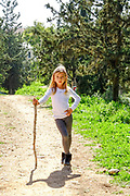 Young girl leans on stick ready for a hike in a nature reserve. Model release available