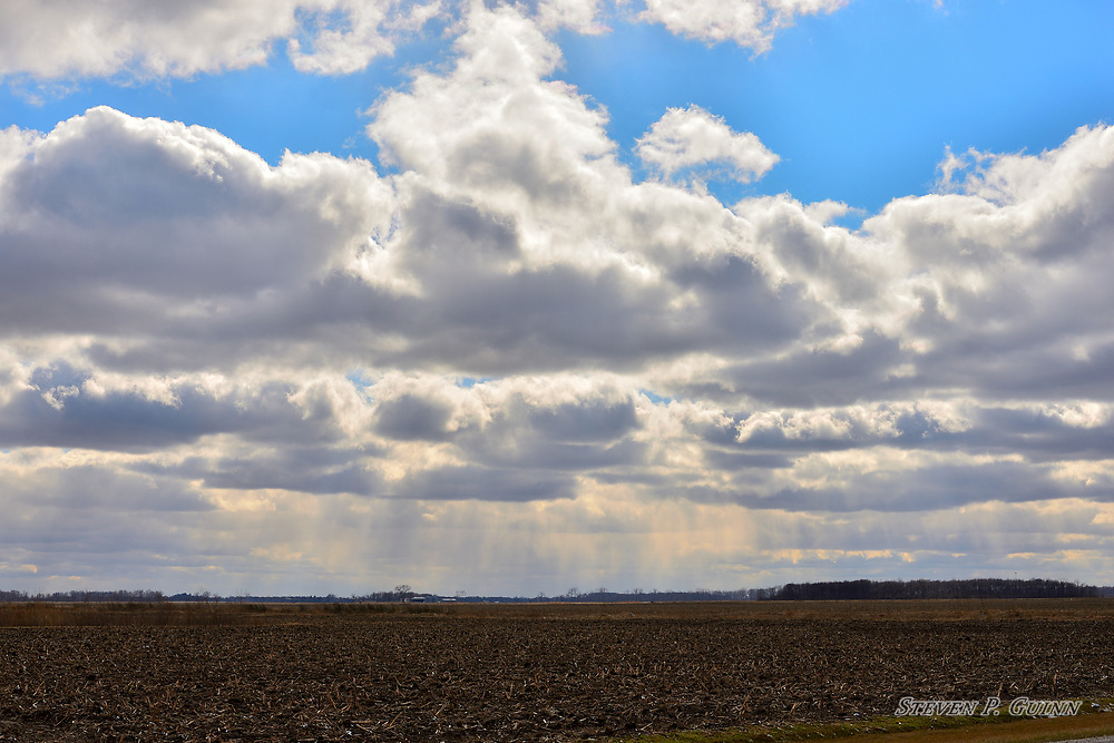 """I captured this landscape over a harvested farm field in Demotte, Indiana on March 7th, 2018. While I was driving through Demotte, Indiana, I saw these stratocumulus cloud formations with sunlight shining through them in the background and decided to pull over to photograph it. I was most drawn to the way the sunlight was shining through the gaps of the cloud formations and reflecting off of the water vapor and rainfall in the distance. The way the mix of dark grays with light grays and whites gives the clouds a three-dimensional appearance stood out to me as well. <br /> <br /> Printed on Hahnemühle German Etching paper. Limited to 100 productions per size.<br /> <br /> Framed prints are available in 18"""" x 12"""", 24"""" x 16"""", 30"""" x 20"""", 36"""" x 24"""", 45"""" x 30"""", and 60"""" x 40"""" sizes."""