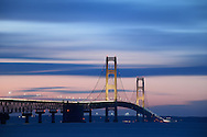 Swiftly moving clouds pass over the Mackinac Bridge at dusk