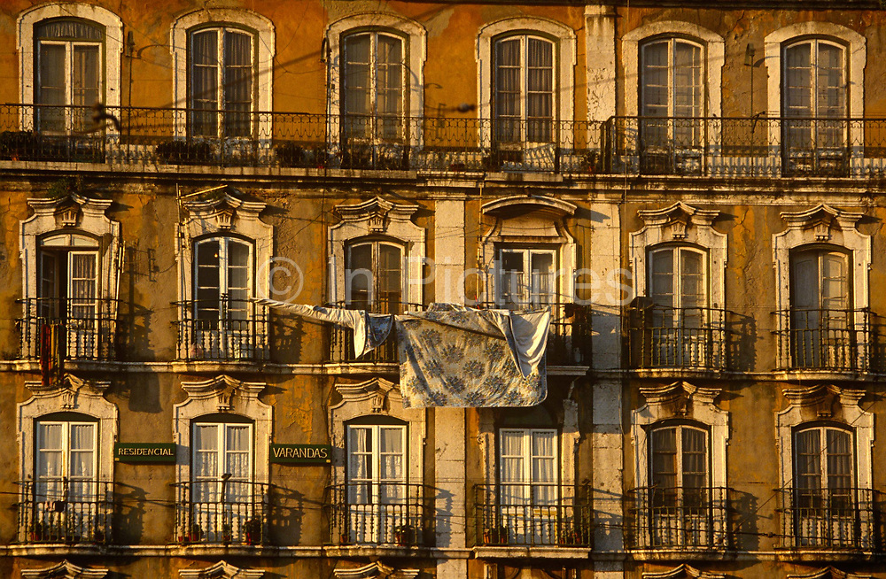 In late afternoon sunshine we see washing hanging on old railings and balconies of some old apartments in Lisbon's old Alfama district. Two signs tell us the buildings are called Residencial Varandas and the crumbling windows and balconies look vintage and classical from a former era in Lisbon's capital. Alfama is the oldest district of Lisbon, spreading on the slope between the Castle of Lisbon and the Tejo river. Its name comes from the Arabic Al-hamma, meaning fountains or baths. It contains many important historical attractions, with many Fado bars and restaurants.