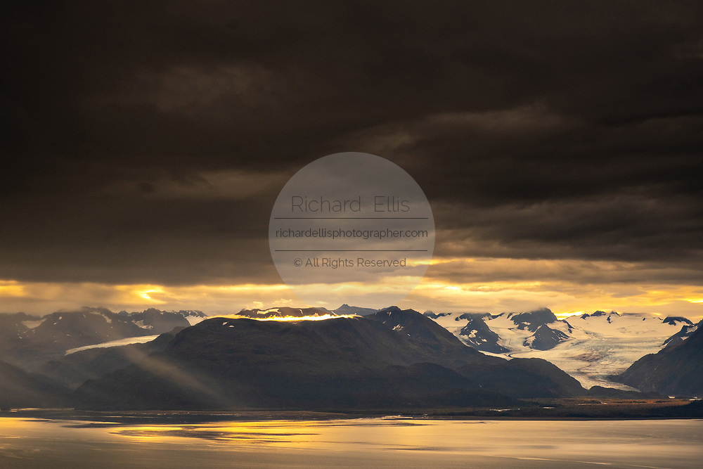 Storm clouds part at sunset over Grewingk Glacier along the Kachemak Bay State Park from Homer, Alaska.