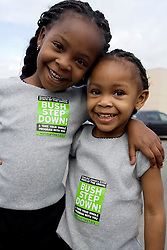 16 Jan, 2006. New Orleans, Louisiana. Post Katrina.<br />  Martin Luther King Jr parade. Girls L/R Cazell Monroe (6 yrs) and her sister Tayzell (3yrs) take up early activism at the C3/Hands off Iberville coalition march which travels almost 6 miles from the devastated Lower Ninth Ward to downtown New Orleans in an alternative protest to the Mayor's officially sanctioned celebrations marking Martin Luther King Jr day. The protest remembered those who perished and claims to stand up for the rights of displaced, primarily african americans.<br /> Photo; Charlie Varley/varleypix.com