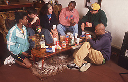 Group of teenagers drinking alcohol and smoking cigarettes at house party,