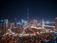 Aerial view of Dubai skyline with Burj Khalifa world's tallest skyscraper at night with Dubai creek in foreground, United Arab Emirates.