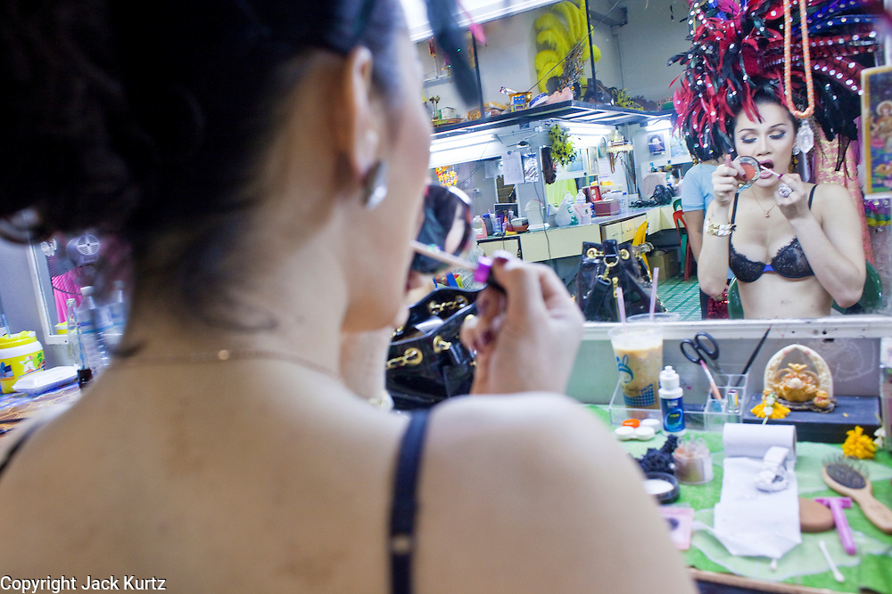 "Oct. 7, 2009 -- BANGKOK, THAILAND:  A ""Ladyboy"" puts on her makeup before performing the Mambo Cabaret. The performers at the Mambo Cabaret in Bangkok, Thailand are all ""Ladyboys,"" or kathoeys in Thai. Recognized as a third gender, between male and female, they are born biologically male but live their lives as women. Many kathoey realize they are third gender in their early teens, some only as old 12 or 13. Kathoeys frequently undergo gender reassignment surgery to become women. Being a kathoey in Thailand does not carry the same negative connotation that being a transgendered person in the West does. A number of prominent Thai entertainers are kathoeys. Photo by Jack Kurtz / ZUMA Press"