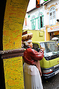 Life-size statue of a cook or baker, standing beside graffiti-covered archway. Little India, Singapore