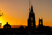 Colorful sunset over the bell towers of the Parroquia de San Miguel Arcangel and the lesser San Rafael Church in the historic city center in San Miguel de Allende, Mexico.