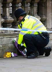 Westminster, London, March 23rd 2017. A [police officer adjusts bouquets of flowers blown over by the wind on Whitehall as investigations continue following Tuesday's terrorist attack on Westminster Bridge and in the grounds of Parliament, in which four people and their attacker were killed with over 40 injured.