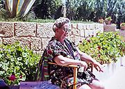 Elderly woman sitting in chair alone smoking  sitting in sunshine outdoors in Mediterranean location 1966