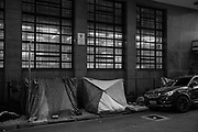 Tents of homeless people made of donated blankets on a street in downtown São Paulo. Many families who lost income or became unemployed because of the economic crisis generated by the pandemic, could no longer pay their rent and had to leave their homes. Without housing options, these families invaded land in the outskirts and occupied abandoned buildings in the city centre, or went to live on the streets.