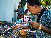 27 NOVEMBER 2015 - BANGKOK, THAILAND: A man looks at amulets on Maharat Road in Bangkok. Hundreds of vendors sell amulet and Buddhist religious paraphernalia to people in the Amulet Market, a popular tourist attraction along Maharat Road north of the Grand Palace near Wat Maharat in Bangkok. Bangkok municipal officials announced that they are closing the market and forcing vendors to relocate to an area about one hour outside of Bangkok. The closing of the amulet market is the latest in a series of municipal efforts to close and evict street vendors and markets from areas that have potential for redevelopment. The street vendors will be evicted from the area by Sunday, Nov. 29.    PHOTO BY JACK KURTZ