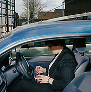 Sally Williams drinks promotions and sales coordinator for GSK products working in Maidstone.  She is photographed in a car park checking her diary. Sally is constantly on the go checking the stock levels and other issues of all the individual shops in her area. Having good mobile communication tools are essential in her business. She is a mother and works part time so the flexible working hours of her job are attractive. From the series Desk Job, a project which explores globalisation through office life around the World.