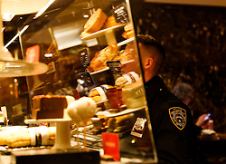 A security officer buys a coffee, in the second floor of the Trump Tower, while President elect Donald Trump is holding meetings on top floors of the building, November 21, 2016, in New York, NY. (Aude Guerrucci / Pool)