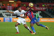 Wilfried Zaha of Crystal Palace ® is challenged by Kyle Naughton of Swansea city. Premier league match, Swansea city v Crystal Palace at the Liberty Stadium in Swansea, South Wales on Saturday 23rd December 2017.<br /> pic by  Andrew Orchard, Andrew Orchard sports photography.