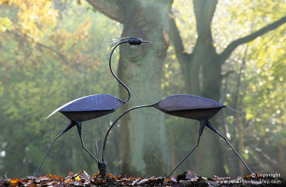 Decorative steel heron statues in autumn