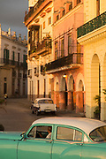Buildings with colonial architecture and vintage car on city street, Havana, Cuba