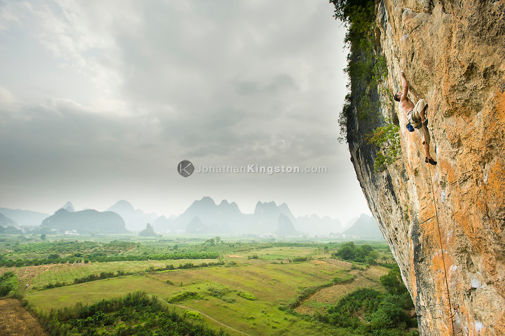 A male rock climber scales an orange cliff at an area known as The White Mountain near Yangshuo, China (Model Released, Sean Ouyang).