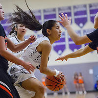 Miyamura Partiot Phrankie Pawlowski (12) snatches a rebound away from Gallup Bengal Sara Ann Shirley (23) Friday at Miyamura High School.