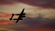 Lockheed P-38 L Lightning flying at sunset.