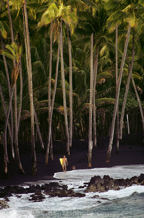 Surfer on volcanic black sand Kaimu Beach, Big Island, Hawaii. USA.