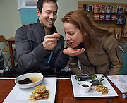 """Mara Lavitt /For Hearst Connecticut Media<br /> February 6, 2016<br /> Catch A Healthy Habit Cafe, Fairfield. Robert Petrucci of Norwalk, left, gives Ann Kokkinos of Norwalk a taste of his miso soup. On his plate is a tomavo made of nut pate, tomato, avocado, on onion """"bread"""" of ground flaxseed, ground sunflower seed, pureed onions and olive oil with Rawmesan (a commercial product of walnuts, sunflower seeds, nutritional yeast and salt); on her plate is a nori wrap: nori, fig marmalade, cashew """"cheese,"""" beet, sunflower sprouts, avocado, crispy onion, spinach, """"salt & vinegar"""" zucchini chips all with a dipping sauce."""