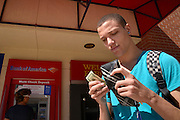A young man with a wallet and money on a college campus.